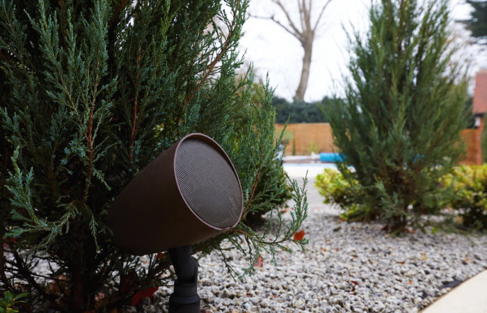 Brown outdoor speaker nestled into shrubbery and plants to disguise itself
